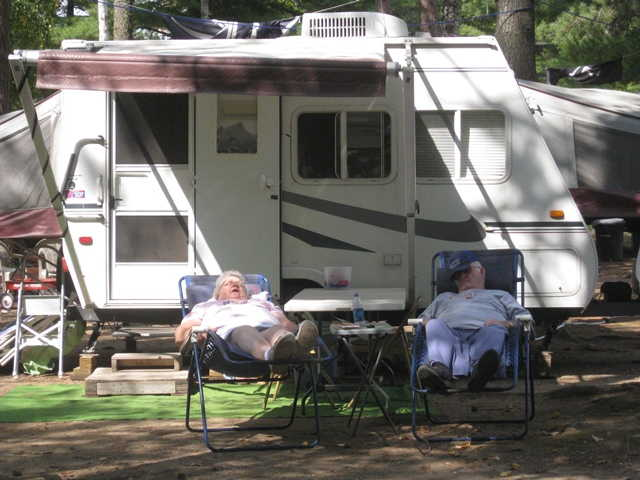 Chain O' Lakes Campground -- couple snoozingi n front of their RV